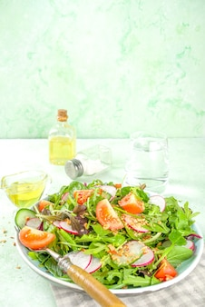 Fresh colorful spring salad with tomatoes, avocado, walnuts, cucumber, spring radish, on light green background copy space. spring diet healthy food concept
