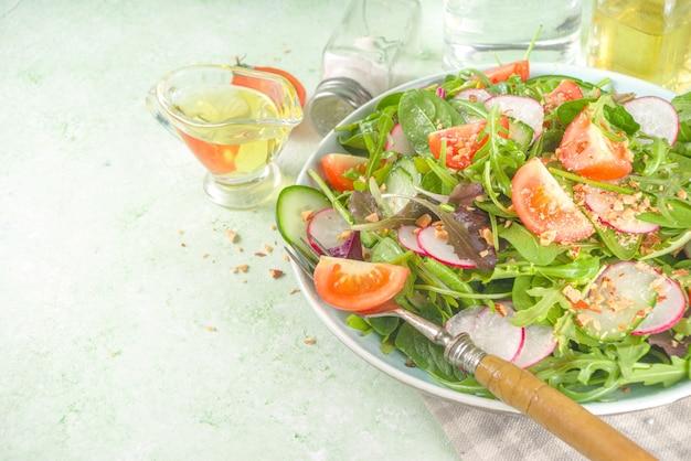 トマト、アボカド、クルミ、キュウリ、春の大根、薄緑色の背景のコピースペースで新鮮なカラフルな春のサラダ。春のダイエット健康食品の概念