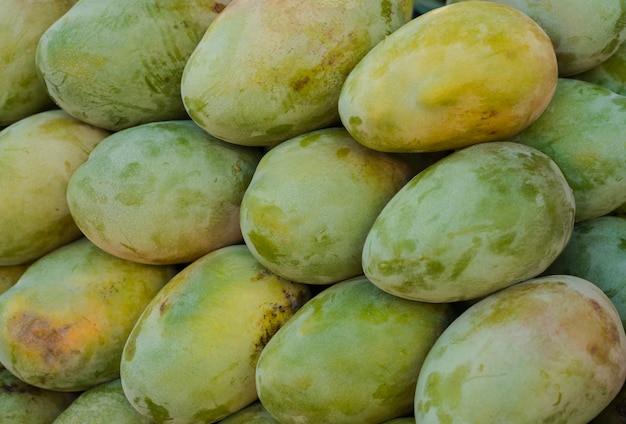 Fresh colorful tropical mangoes on display at outdoor farmers market close-up.