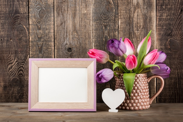 Fresh colorful tulips, white heart and blank wooden frame