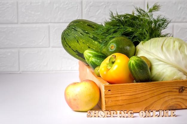 木製の箱に新鮮な色とりどりの野菜。白色の背景。オンライン食料品の買い物。