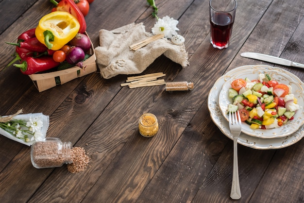 暗い背景の木の白い皿に新鮮なカラフルな野菜