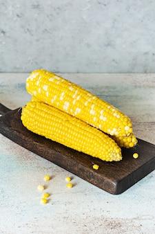 Свежая вареная (вареная) кукуруза на деревянной доске на сером (синем) фоне. зрелая кукуруза.