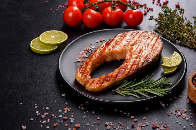 Свежеприготовленный вкуснейший стейк из лосося со специями и зеленью, запеченный на гриле. здоровая еда из морепродуктов