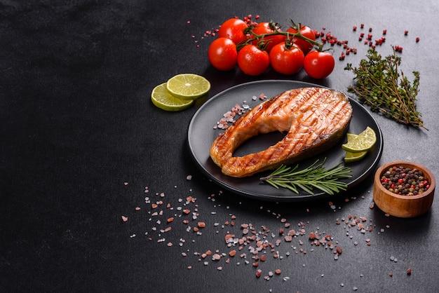 Свежеприготовленный вкусный стейк из лосося со специями и зеленью, запеченный на гриле