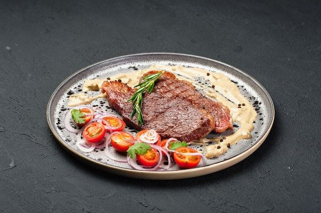 Fresh cooked meat on metallic plate sliced tomato