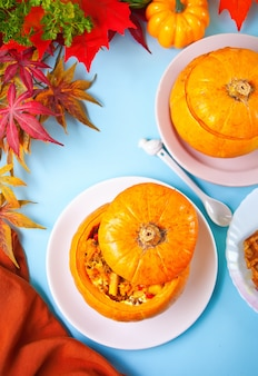 Fresh cooked pumpkin soup served in a pumpkin. stuffed pumpkin. autumn warm and cozy food. top view.