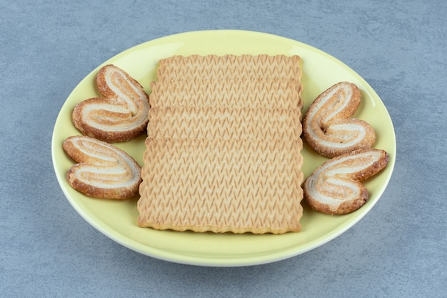 黄色のセラミックプレートに新鮮なクッキー。写真をクローズアップ。