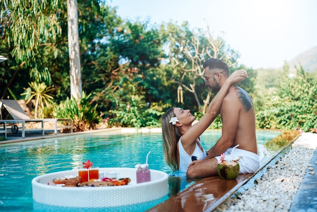 Fresh and cool asian food on floating table in swimming pool. loving guy and girl hug each other around swimming pool in hotel.