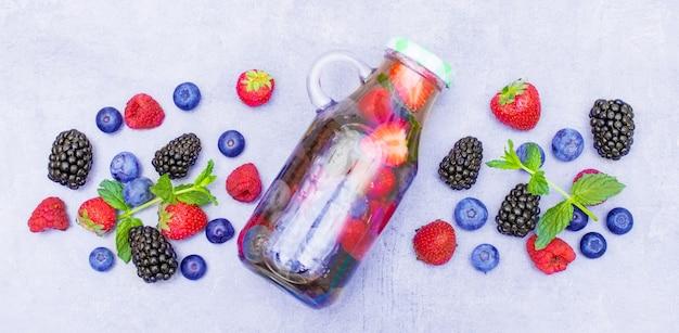 ガラスの瓶に、新鮮な冷たいベリーとミントを注入した水、デトックスドリンク。