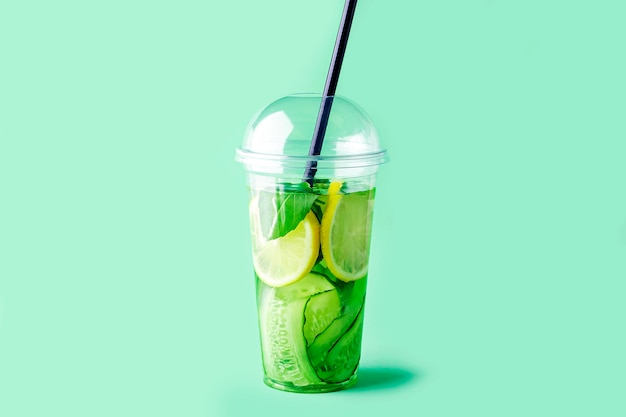 Fresh cool detox drink with cucumber, lemon and basil in plastic cup on green