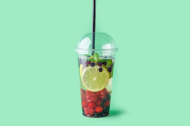 緑の背景にプラスチック製のコップにさまざまなベリーと新鮮なクールなデトックスドリンク。おいしい注入水またはレモネードをお持ちください。適切な栄養と健康的な食事。フィットネスダイエット。メニュー用のテキスト用のスペースをコピーします。