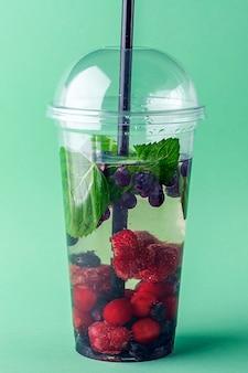 緑の壁にプラスチック製のコップにさまざまなベリーと新鮮なクールなデトックスドリンク。おいしい注入水またはレモネードをお持ちください。適切な栄養と健康的な食事。フィットネスダイエット。