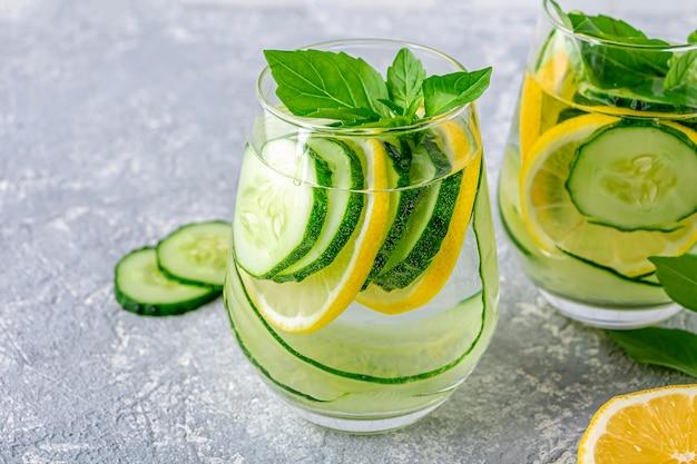 きゅうりとレモンの入った新鮮な冷たいデトックスウォータードリンク。バジルとミントの葉が入ったレモネード2杯。適切な栄養と健康的な食事の概念。フィットネスダイエット。テキスト用のスペースをコピーする