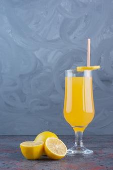 Fresh cool lemon cocktail with lemons on gray surface