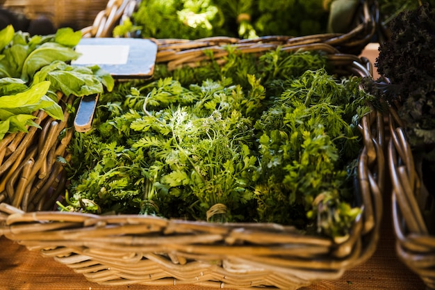 Fresh coriander in wicker basket for sale at supermarket