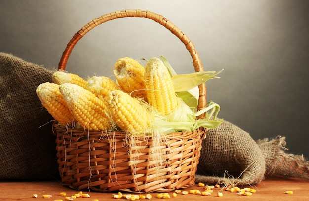 Fresh corn in basket, on wooden table