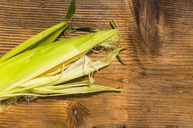 Fresh corn on cob against wooden background
