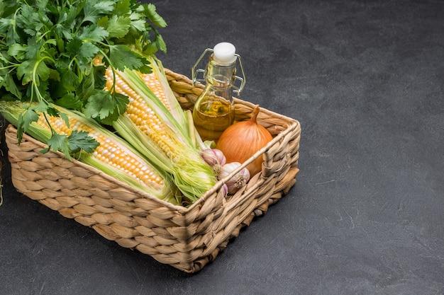 新鮮なトウモロコシの穂軸、パセリの束、ボトルに入った油、籐のかごに入ったニンニク。スペースをコピーします。黒の背景。上面図。
