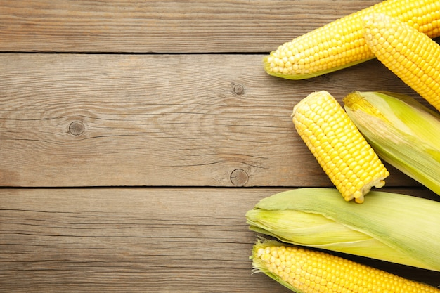 Fresh corn on cobs on rustic wooden table, closeup. top view