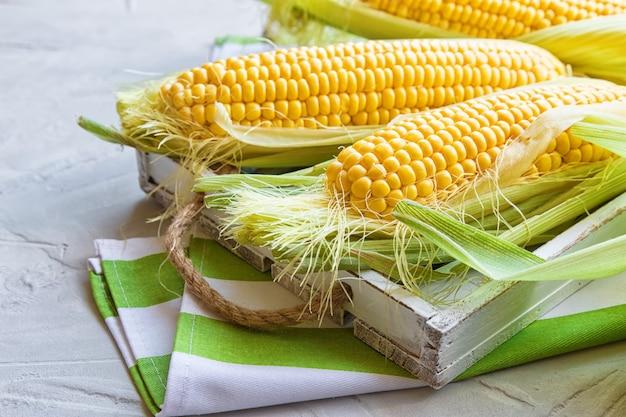 Свежая кукуруза в початках на деревенском деревянном подносе на светло-сером бетоне.