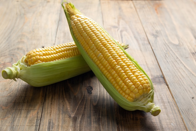 Fresh corn on wooden table.