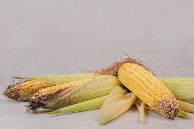 白いテーブルの穂軸の新鮮なトウモロコシ。