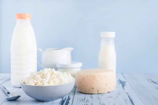 Fresh cottage cheese and bottles of mik on blue background