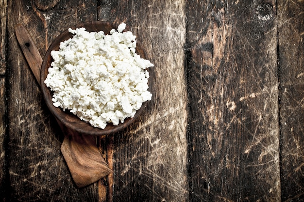 Fresh cottage cheese in a bowl on wooden table.