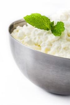 白い背景に分離された金属製のボウルに新鮮なカッテージチーズをクローズアップ