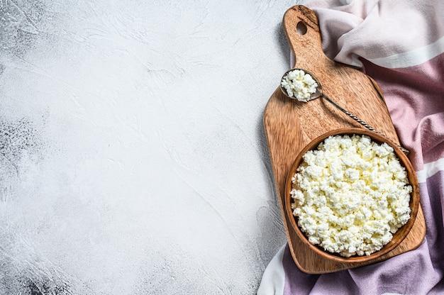 木製のボウルに新鮮なカッテージチーズ。灰色の背景。上面図。コピースペース