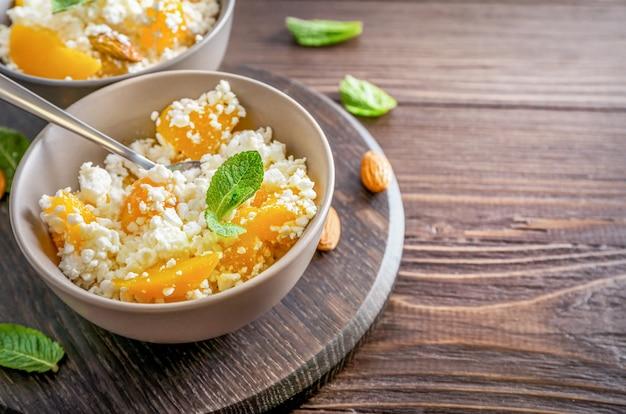 ミントの葉、桃の部分、木製の背景にアーモンドナッツとボウルに新鮮なカッテージチーズ。 Premium写真