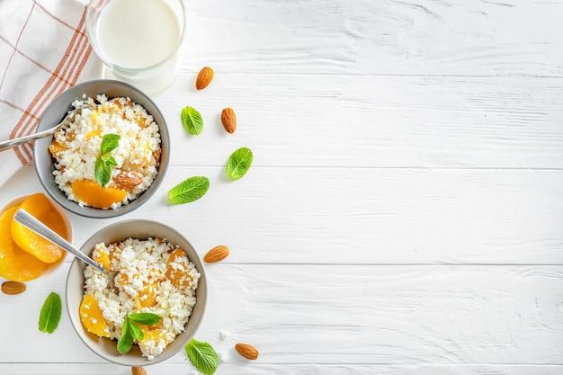 ミントの葉、桃の部分、白い木製の背景にアーモンドナッツとボウルに新鮮なカッテージチーズ。上面図。スペースをコピーします。