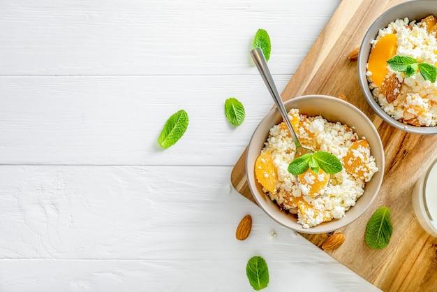 ミントの葉、桃の部分、白い木製の背景の木製まな板にアーモンドナッツとボウルに新鮮なカッテージチーズ。上面図。スペースをコピーします。