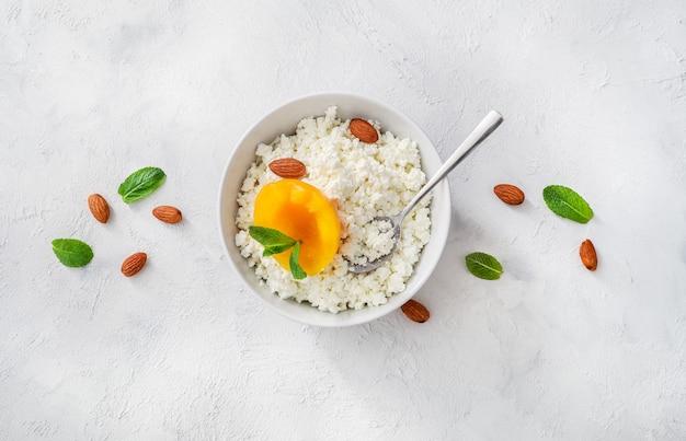 ミントの葉、桃の部分、アーモンドナッツ、白い背景に小さじ1杯の白いボウルに新鮮なカッテージチーズ。上面図。