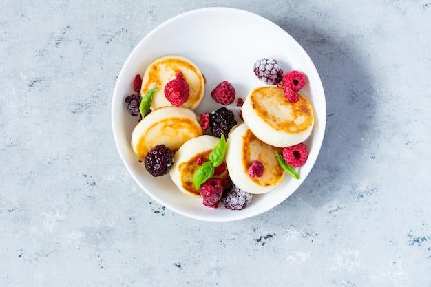 Сырникифриттеры из свежего творога или блинчиков с рикоттой на белой тарелке со свежими ягодами на синем фоне вкусный здоровый завтрак сладкие блюда украинской русской кухни