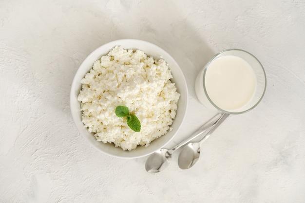 白いボウルにミントの葉、白い背景にミルクと小さじ1杯の新鮮なカッテージチーズ。上面図。