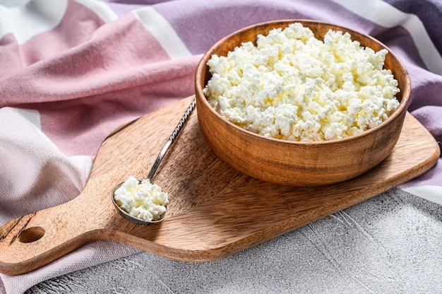 Fresh cottage cheese in a wooden bowl on cutting board. gray background. top view.