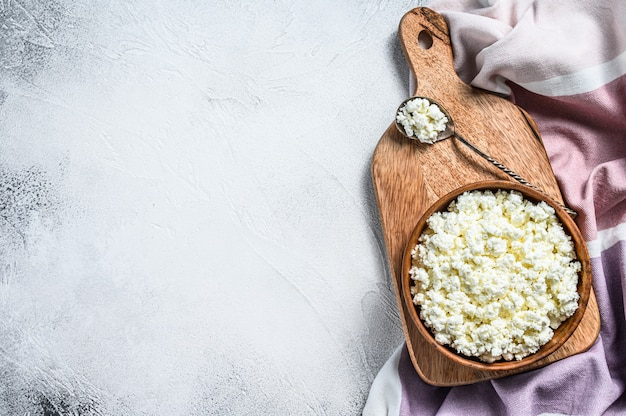 Fresh cottage cheese in a wooden bowl.  gray background. top view. copy space