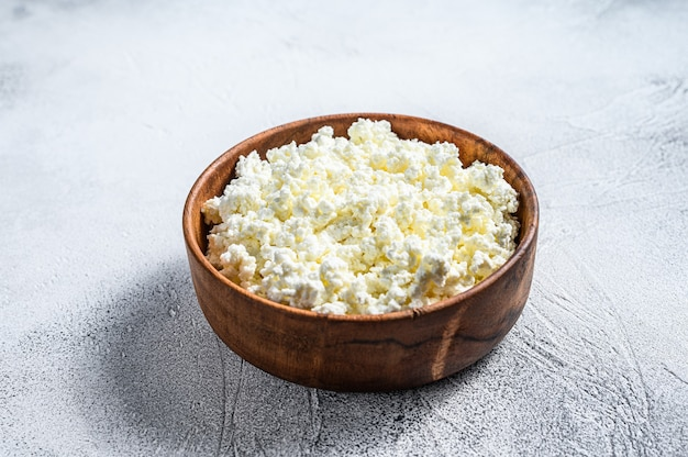 Fresh cottage cheese in a wooden bowl.  gray background. top view.