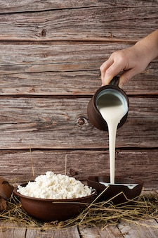 Fresh cottage cheese in a wooden bowl with hand pours sour cream from jar on a wooden