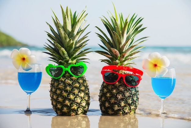 Fresh couple pineapples with sun glasses and cocktail glasses on clean sand beach with sea wave - fresh fruit and drink with sea sand sun vacation concept