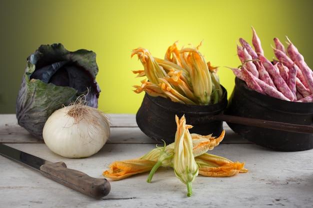 白いテーブルの上に新鮮なズッキーニの花、豆、唐辛子、タマネギ