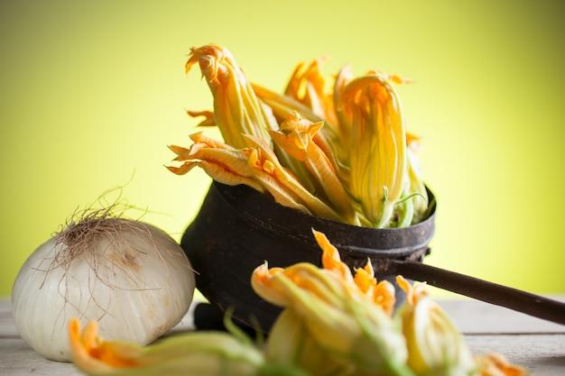 古い銅のボウルの中の新鮮なズッキーニの花