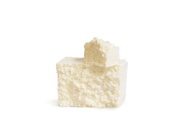 白い背景の上の新鮮な牛のミルクカッテージチーズ