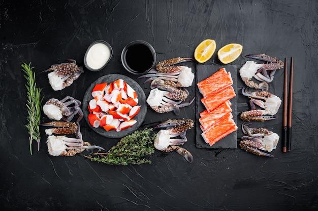 Свежее крабовое мясо и палочки сурими с набором синего плавательного краба, на черном фоне, плоская планировка, вид сверху