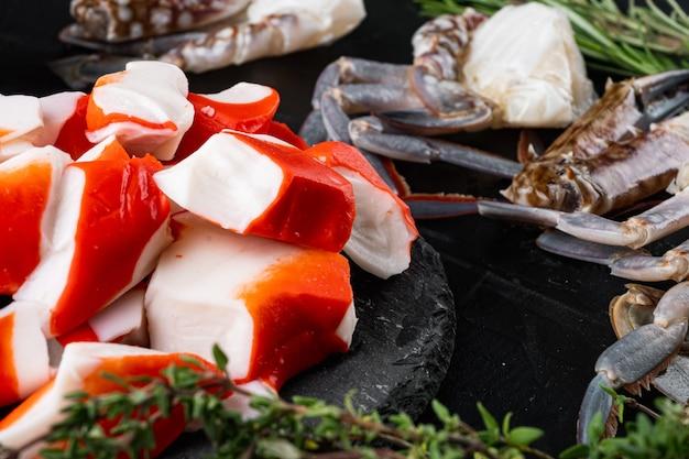 Сурими из свежего крабового мяса с набором синего плавательного краба на черном фоне