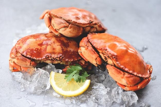 Свежий краб на льду и лимон для салата на тарелке - приготовленные крабы морепродукты