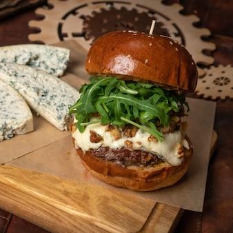 Бургер из свежей говядины со свежим салатом из рукколы и кусочками свежего голубого сыра, лежащими рядом.