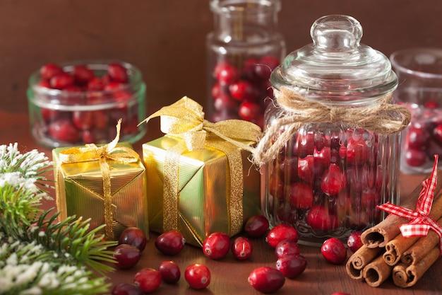 Свежая клюква в стеклянных банках, зимнее украшение и подарки